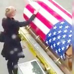 Blonde woman is escorted off plane, approaches coffin without realizing she's being filmed.