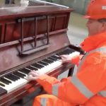 Workman starts to play on train station piano, people stop mesmerized as fingers fly across keys.