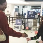 Strangers hand unaware woman a rose at airport. She cries tears of joy when she learns why.