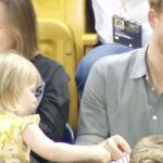Sneaky toddler tries to steal popcorn from Prince Harry but he's happy to share with her.